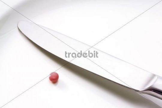 Empty plate with a pill and knife