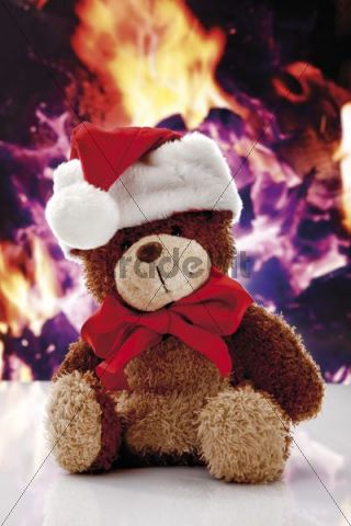 Teddybear with Christmas hat, chimney fire at back