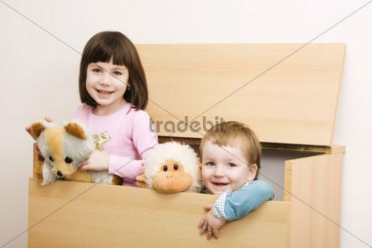 Two sisters, 6 and 3 years, brunette and fair-haired, in hiding place, indoors