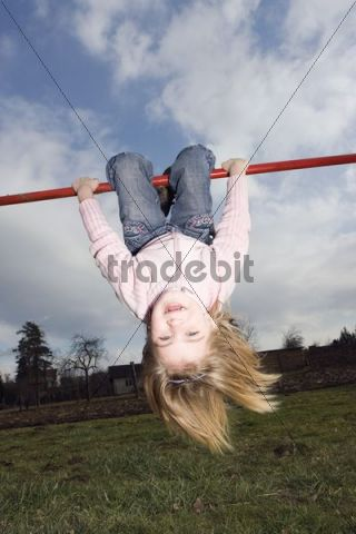 Fair-haired little girl, 6 years, playing on the cross-bar