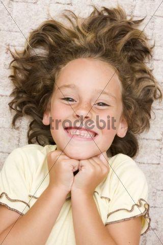 Smiling girl, 6 years old, lying on the floor