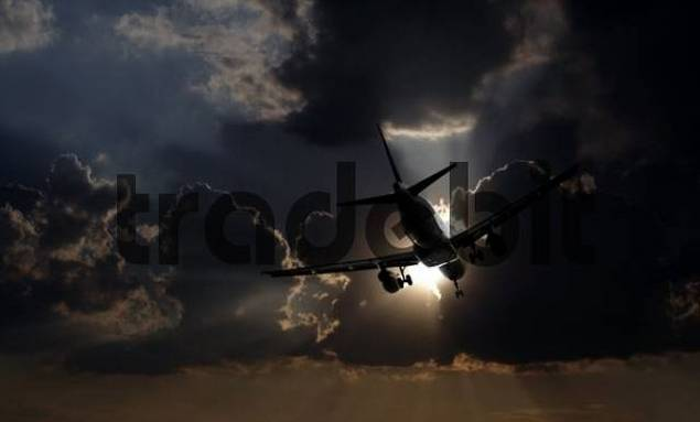 airplane flying towards the sun and stormy clouds
