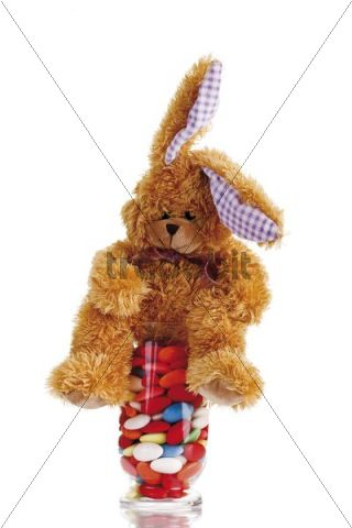 Easter bunny soft toy with candy easter eggs in a glass