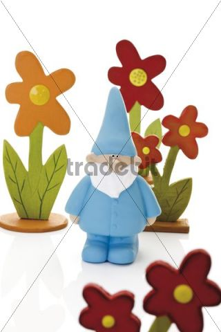 Blue garden gnome standing in the middle of colored wooden flowers