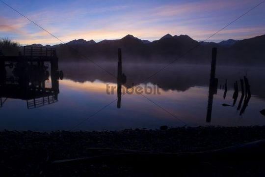 Reflections in the water of the Richardson Mountains at sunrise at Lake Wakatipu, Glenorchy, Otago, South Island, New Zealand