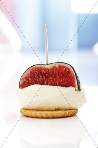 Finger food, mascarpone cheese and fig on a cracker