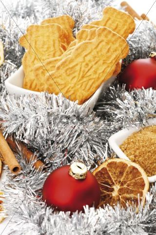 Spiced biscuits in a white bowl and christmas decorations, cinnamon sticks, orange slices and christmas tree balls