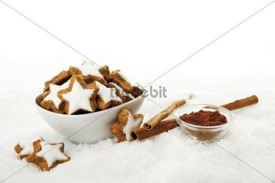 Cinnamon star-shaped biscuits with sticks of cinnamon and cinnamon in artificial snow