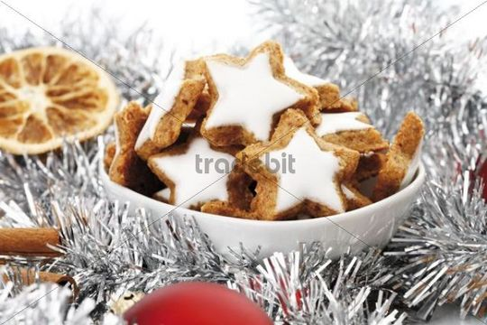 Cinnamon flavored star-shaped biscuits, christmas decorations, Cinnamon sticks, slices of orange and christmas tree balls