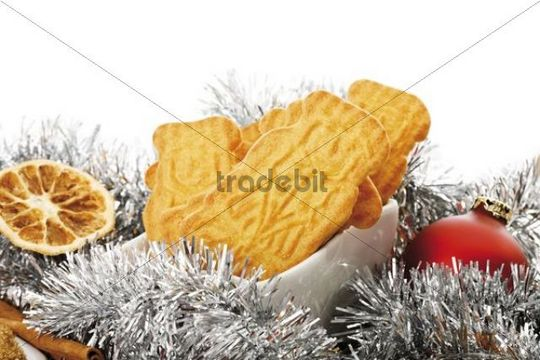Spiced biscuits in a white bowl, christmas decorations, cinnamon sticks, orange slices and christmas tree balls