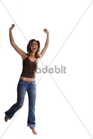 Young woman with dark blond hair, jumping and dancing with her arms raised, wearing brown t-shirt and jeans, bare feet