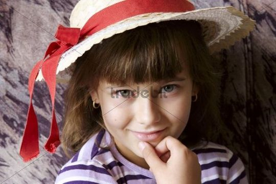 Girl wearing a hat with red ribbon