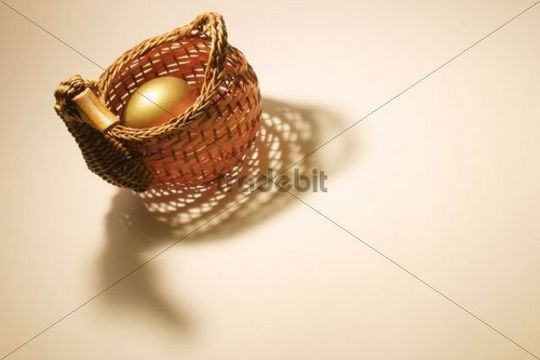 Golden egg tucked in a basket