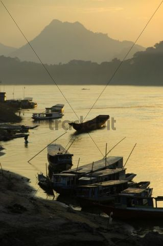 Sunset sky with boats on the shore of the Mekong River, Luang Prabang, Laos, South Asia