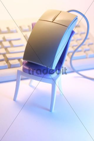 Computer mouse perched on a mini chair, keyboard