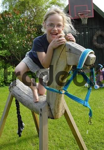 girl balaciert on wood horse