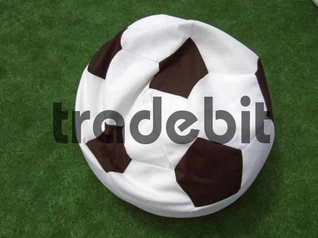 Zerknautschtes Sitzkissen in Form eines Fußballes auf grünem Kunstrasen