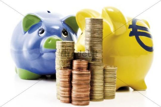 Stack of coins in front of piggy banks
