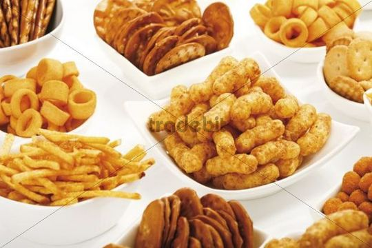 Various spiced snacks in bowls, crisps, peanut flips, pretzel sticks, potato sticks and salted cookies