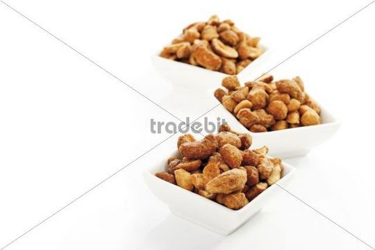 Cashew nuts with salt and honey in white bowls