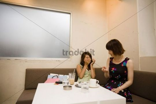 Two young women laughing while sitting in a cafe, Tokyo, Japan, Asia