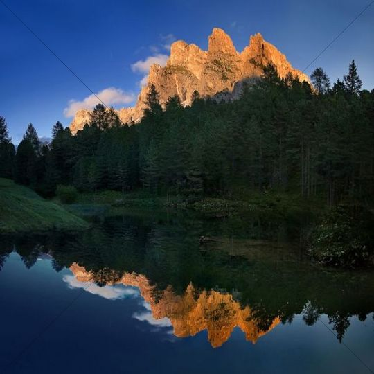 Small lake on the Seceda High Plateau with a reflection of the Stevia mountains, Puez-Geisler National Park, Wolkenstein, Alto Adige, Italy, Europe