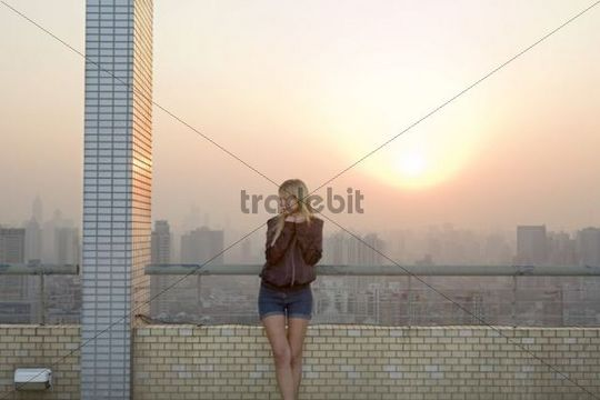 Young woman on a roof terrace in Shanghai, China, Asia