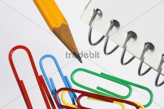 Colored paper clips, pencil and spiral notebook, detail