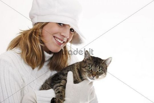 Young woman in a white turtleneck sweater with woolen hat holding a cat