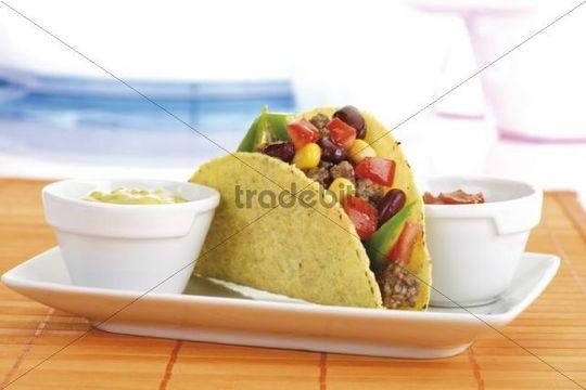 Taco shell with chili con carne, guacamole and tomato salsa