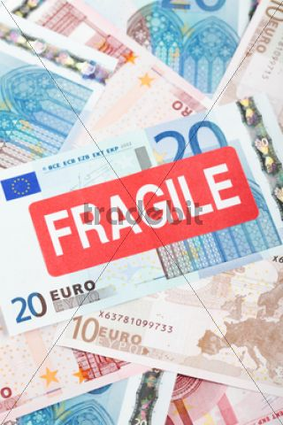 "Euro banknotes with a """"Fragile"""" sticker, symbolic image for the eurozone crisis /"