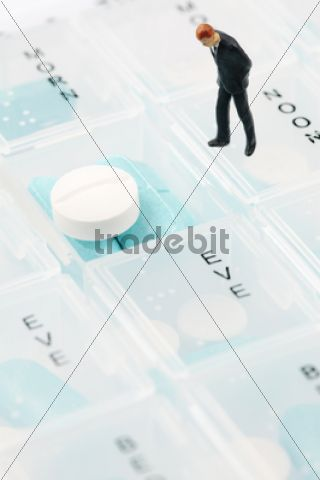 Businessman miniature figurine on pill box /
