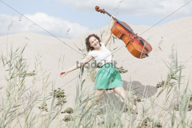 Young woman with cello on a sandy hill