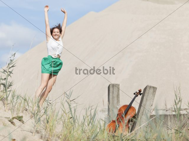 Young woman with cello on a sandy beach