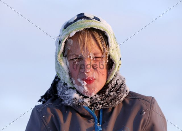 Boy, 11 years, with snow on his face and hood, pulling a face /